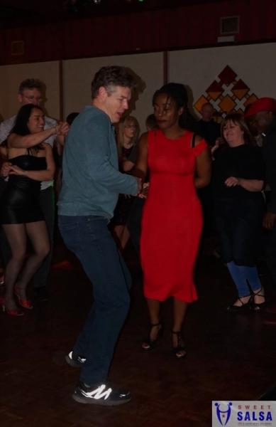 Two people salsa dancing. Lady in a red dress